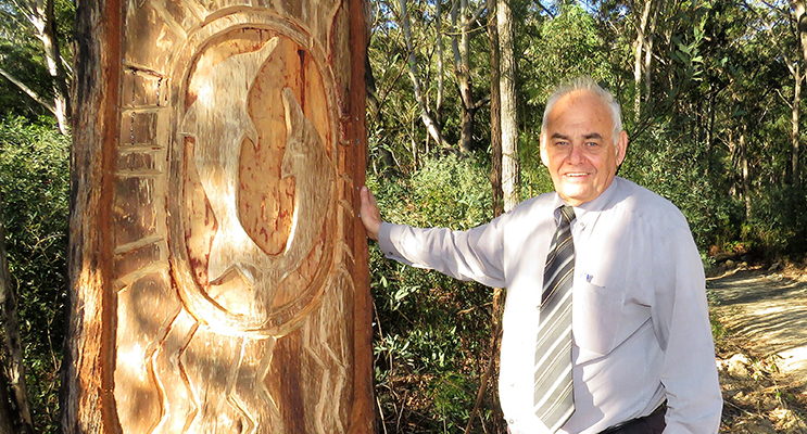 Len Roberts at the tree carving of dolphins at the base of Alum Mountain.