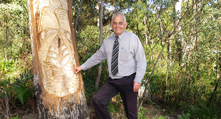 Land Council CEO Len Roberts at the tree carving of a whale at the heads.