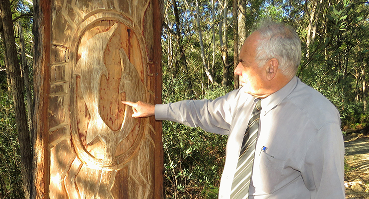 Land Council CEO Len Roberts examines the dolphin tree carving.