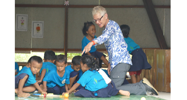 Adrienne Ingram hands out educational toys to pre-school children in Cambodia.