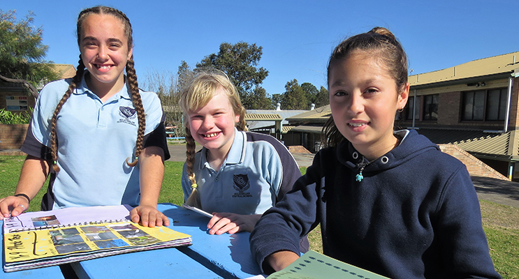 BCS Year 9 student Tahlia Mancini practices for the K-12 Spelling Bee with Year 6 students Maggie Cunich and Maddi Tassell.