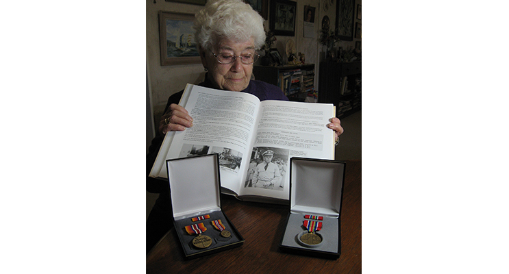 Never forgotten – Margaret reflects on a photo of Frede in Bill Lunney's 'Forgotten Fleet 2.' His service medals are beside the book.
