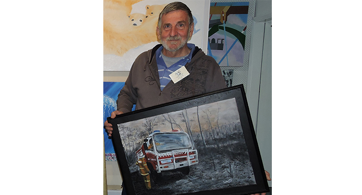 John Crew with his artwork that can be viewed at the exhibition.