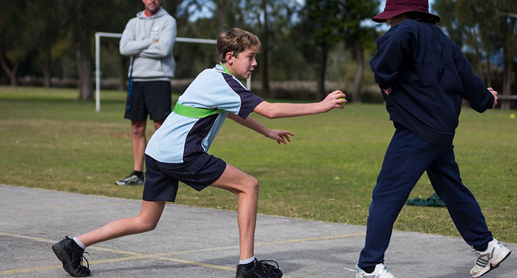 Physical Education: BCS Year 8 student Dane Pope joins in a game of grenade with Year 6 students at Tea Gardens. Photo: BCS