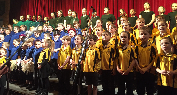 The combined schools choir singing the national anthem.