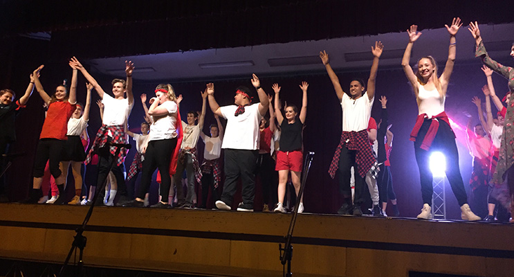 Year 12 students participating in their last showcase perform together and take a bow.