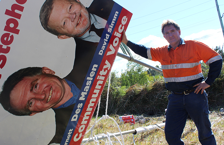 Des Maslen works to repair the sign on Nelson Bay Road.