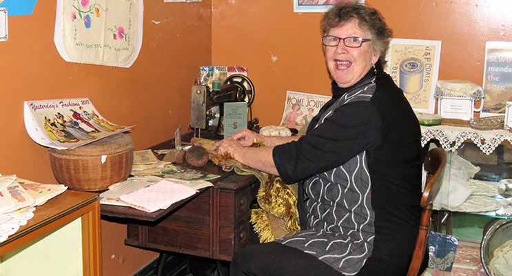 Diane Burns with a sewing machine on display at the Courthouse Museum.