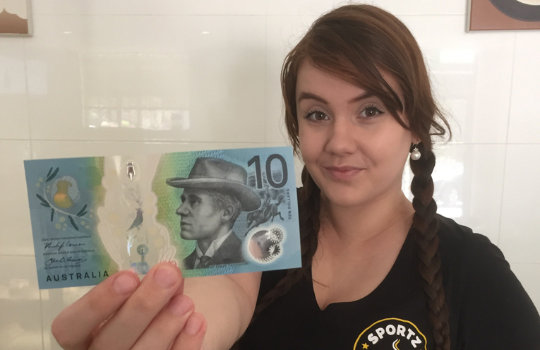 Barista Nyssa Oehm with the first new $10 note to come across the counter at Sportz Cafe.