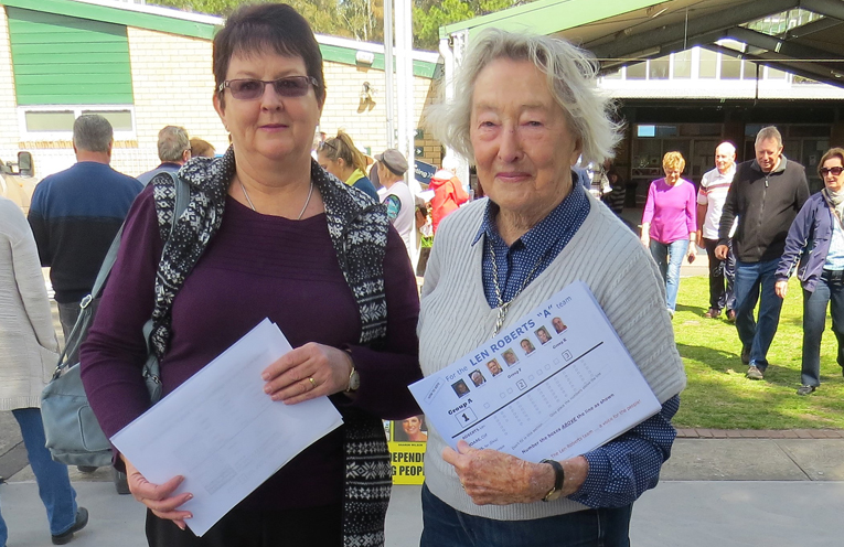 Stephanie Weeks receives a how to vote card from 'A Team' volunteer Marcia Dane in Tea Gardens.