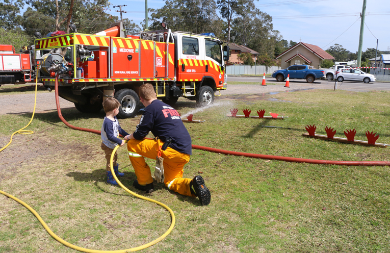 Children were taught how to hold the fire hose, and had fun knocking down the fire cutouts.