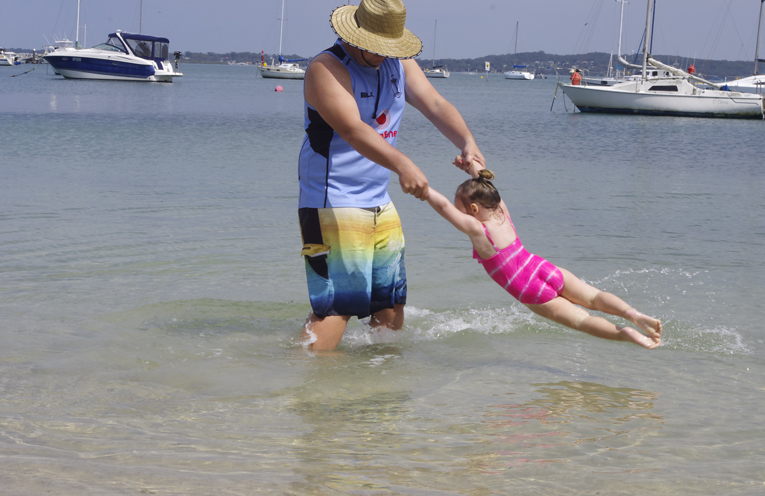 Indiana with her father Lucas Mccleer at the beach adjacent to Soldiers Point Marina. Photo by Marian Sampson