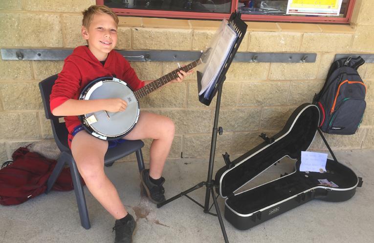 Jack Ryner, 12, busking with his banjo.