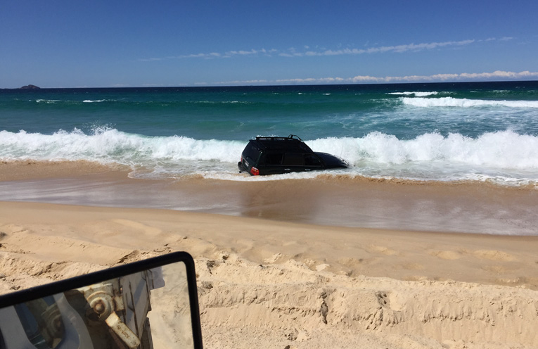 HAWKS NEST: Landcruiser ends up in the surf. Photo: Levi Peters