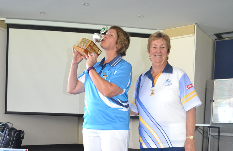 President of Karuah Women's Bowling Club Kim Post, kissing the Trophy with Robyn Webster, President of Tea Gardens Women's Bowling Club.