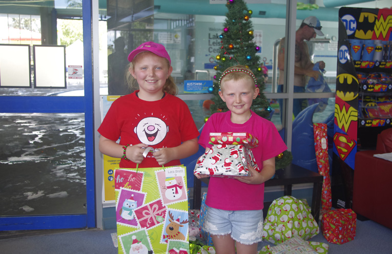 Olivia and Lara Brett at the Camp Quality Christmas party with their Christmas gifts. Photo by Marian Sampson.