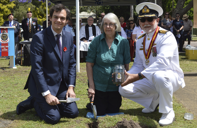 Councillor Giacomo Arnott and Captain Victor Jones, RANR, President of the Raymond Terrace RSL Sub-branch assist the relative of Private Charles Wattus from World War I, collect soil for the Centenary project.