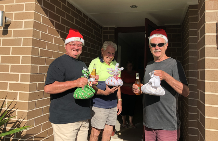 """""""Newby resident"""" Neville Goodwin taking receipt of their Christmas Pudding from Santa and his helper, Pete."""