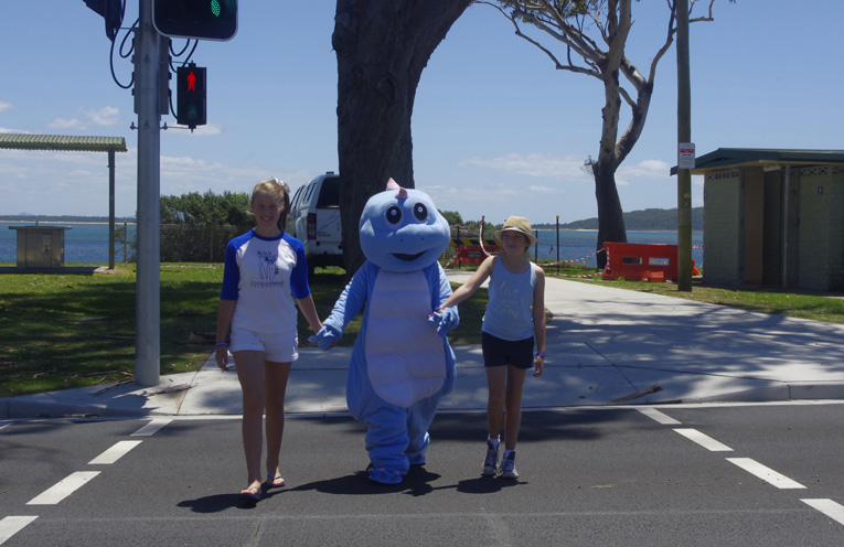 Lucy Hudson The Little Blue Dinosaur and Sophie McLaughlin (Tom's older sister) crossing the road safely at Shoal Bay. Photo by Marian Sampson.