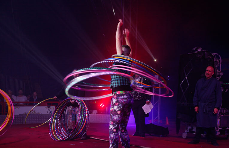 Simon, during part of his routine, having a collection of hula hoops thrown for him to catch on his torso.