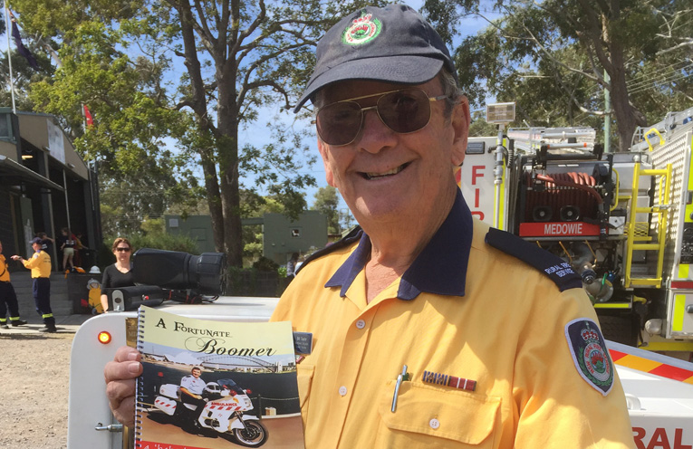 Bill Taylor with his book in front of the mini fire engine he created.