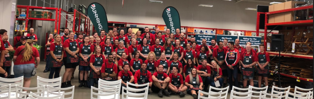 A sea of red and green - staff pose for a photo to mark the official opening of the Heatherbrae store.