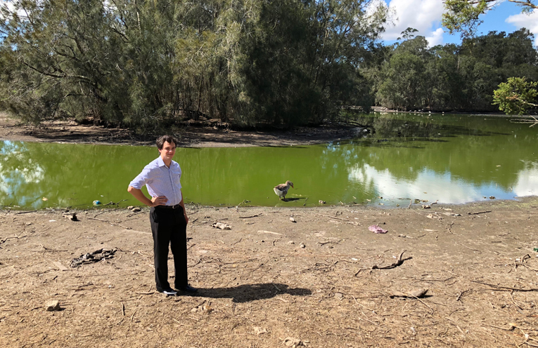 Councillor Arnott standing on the dry bed of the duck pond, which is usually filled with water past this point.