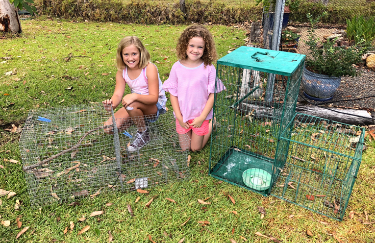 Hannah and Ava Ryder with the two cages their family own to trap Myna birds.