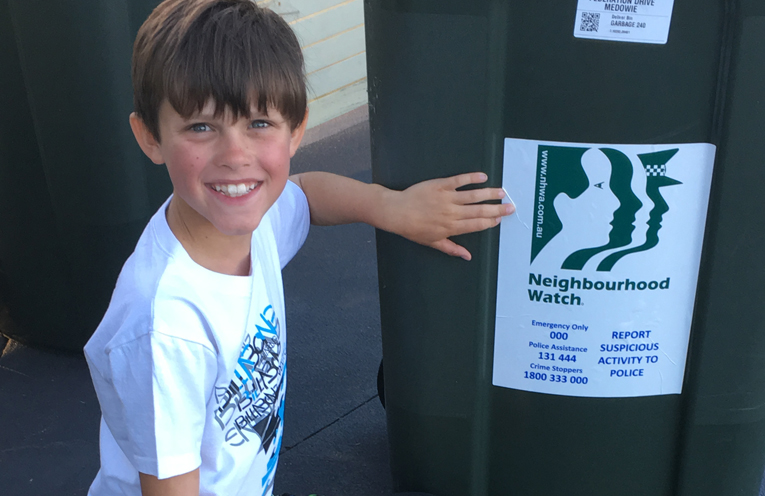 Conner Moore applying the new sticker to his family's wheelie bin.