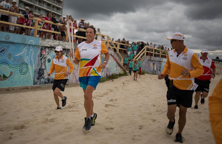 Batonbearer Laura Thurtell carries the Queen's Baton onto Forster Beach.