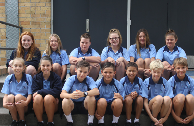 Fresh faced Year 7 students on the steps of the hall at Hunter River High School.