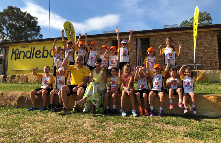 Kate Washington MP with volunteers and athletes at Medowie Little Athletics on their new sandstone tiered seating area.