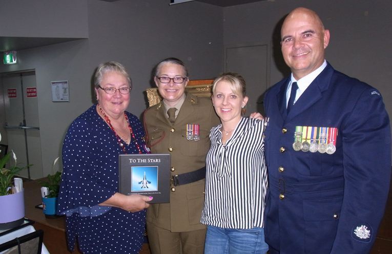 Bugle Cpl Meredith Wilson and President of Raymond Terrace Lions Club Judith Bee, with RAAF, Warrant Officer Rudi Vitasz and his wife Natalli and the book they presented Judith at the event.