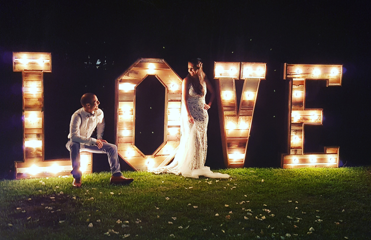 Christy and Nordon McLeod with the 'LOVE' letters on the lawn.