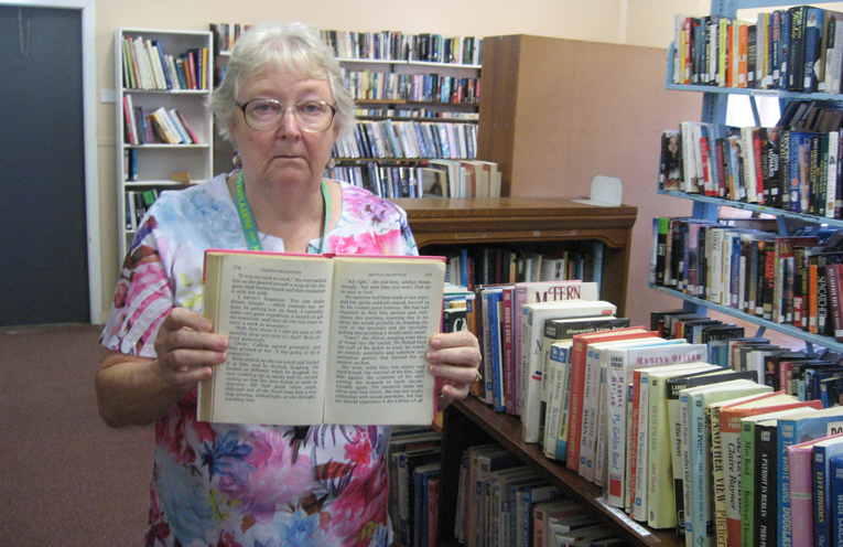 Volunteer Caroline Grimwood with one of the 500 large print books and some of the free magazines on offer.