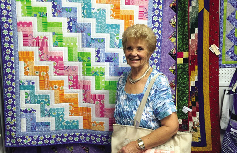 Liz Weiss with one of her quilts.