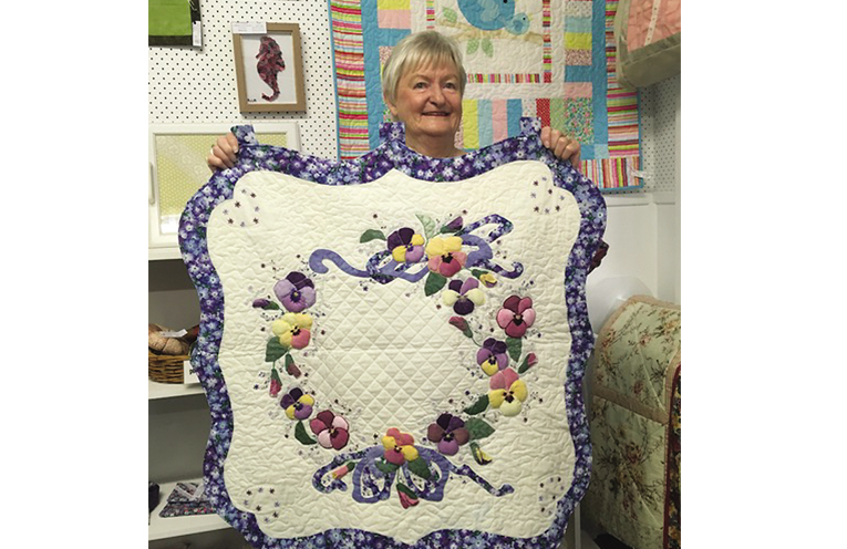 White quilt made by June Roberts.