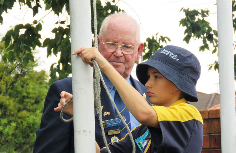 John Renfrew assists a member of the Bulahdelah Scouts with the flags.