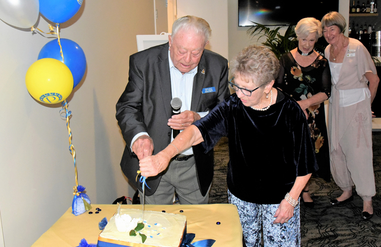 Long time Probus member Doug Pratt cutting the celebration cake with Pam Pett widow of the clubs inagural secretary.
