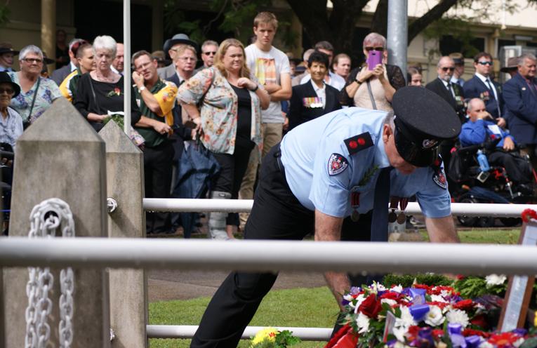 A NSW fire service man lays a wreath.