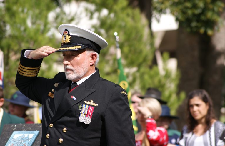 A Navy Officer salutes the cenotaph.