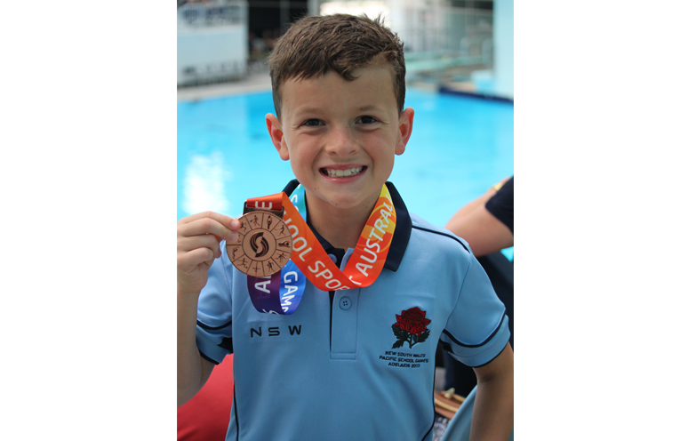 Joshua with one of his medals.