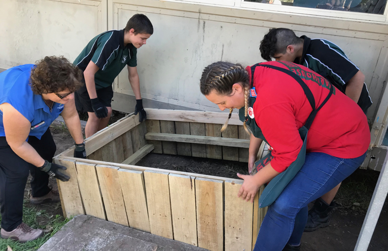 Putting one of the newly constructed garden beds in place at the Learning Alliance classroom.