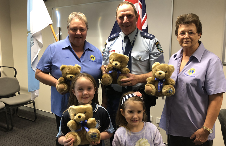 Judith and Inga from Lions Raymond Terrace present some comfort teddies to Inspector Tony Townsend.