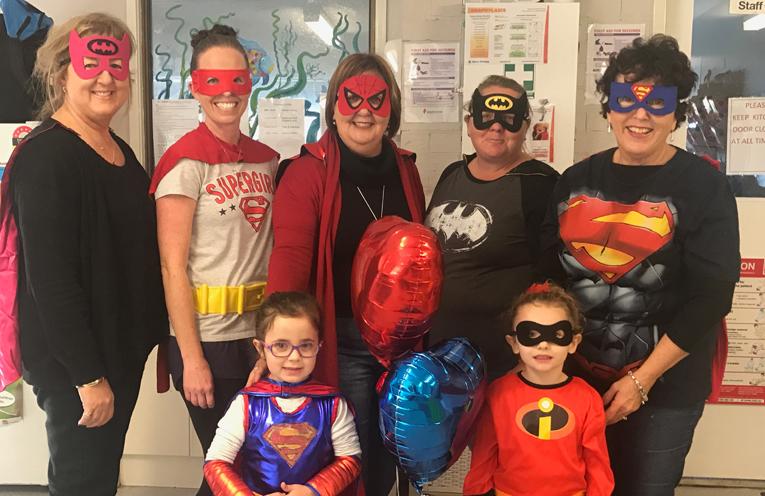 Kaylee with her superhero teachers at Medowie Community Preschool.