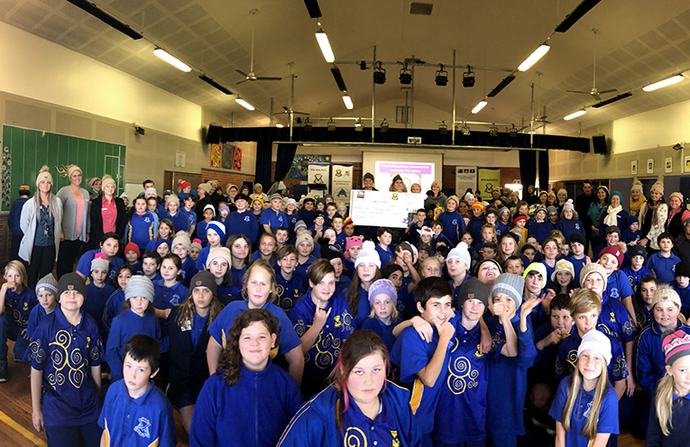 The students of Irrawang Public School with the Twyford family, Mark Hughes and a cheque for $8,777.