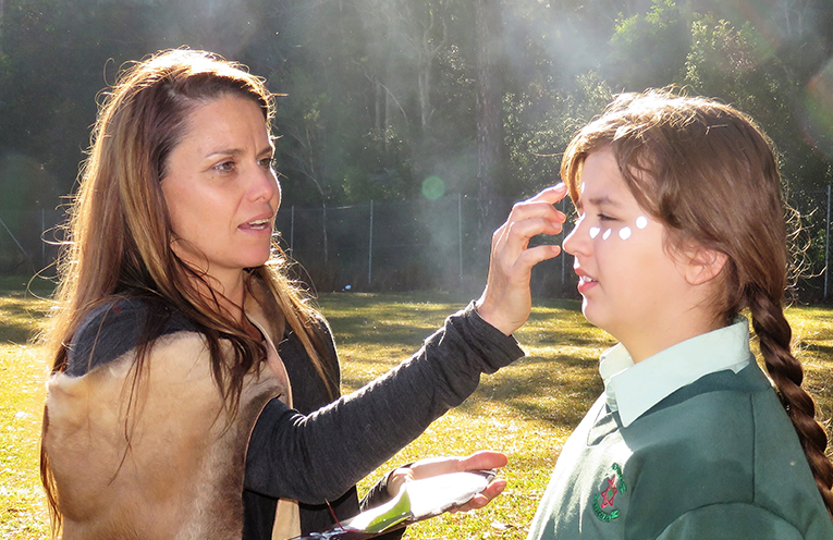 Eve White assists a student prepare for the celebrations at St Joseph's.
