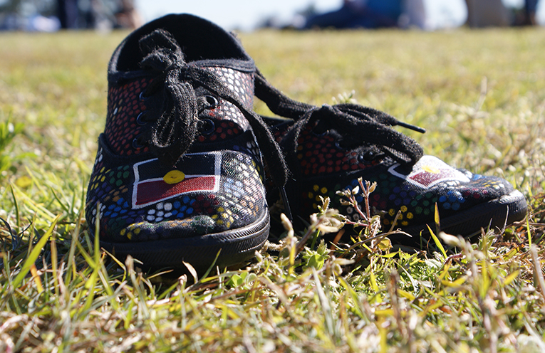 A pair of shoes painted in traditional dot painting, with the Aboriginal flag. Photo by Stelbel Photography.