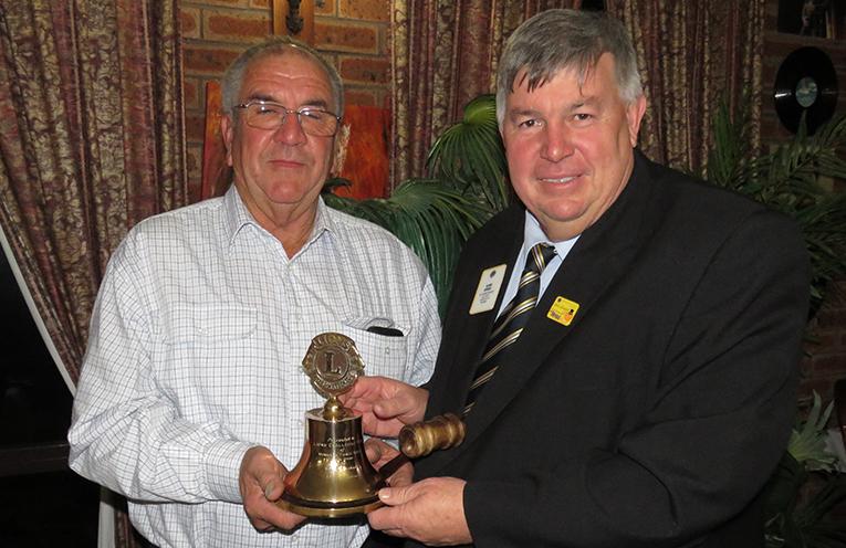 Incoming President Arthur Baker receives the going from District Governor Glenn Byrnes.