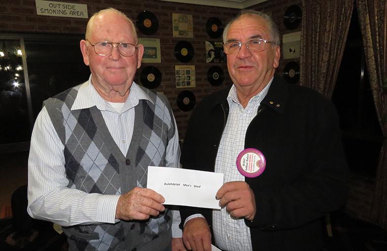 Bulahdelah Men's Shed member John Renshaw receives a donation from Lions President Arthur Baker.